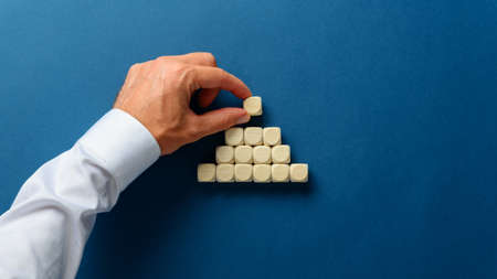 Hand of a businessman making a pyramid shape of blank wooden dices over navy blue background.