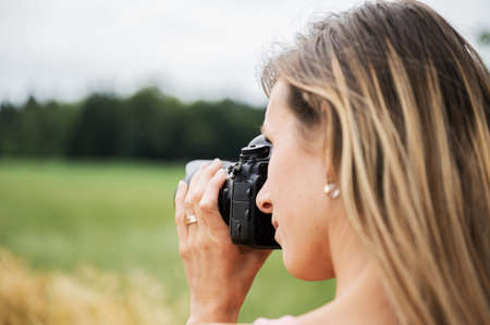 Over the shoulder view of young professional female photographer taking photos outside in nature.