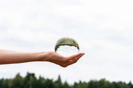 Female hand holding a crystal sphere in which beautiful landscape reflects.