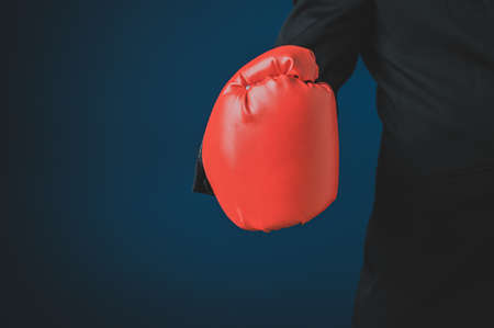 Closeup of a businessman hand in red boxing glove. Over navy blue background.