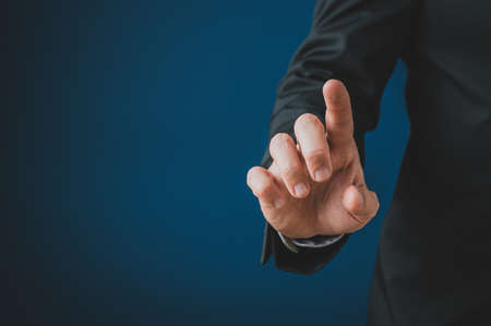 Businessman touching blank virtual screen with his finger. Over navy blue background with copy space.