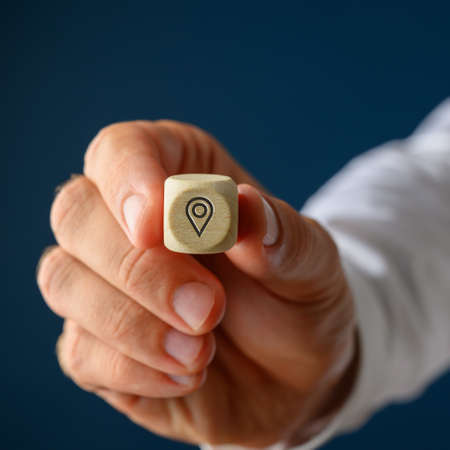Hand of a businessman showing a wooden cube with location pin symbol on it. Over navy blue background. Stock Photo