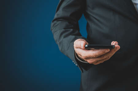 Closeup of businessman in a suit holding smart phone in his hand. Over navy blue background.