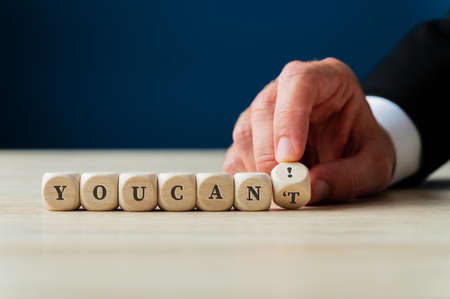 Hand of a businessman changing a You cant sign on wooden cubes in to a You can! by flipping the last dice. Фото со стока