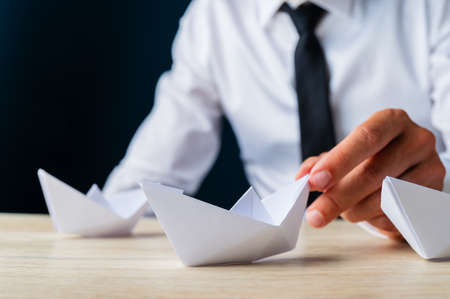 Closeup view of businessman placing paper made origami boat on wooden desk along with the others. 写真素材