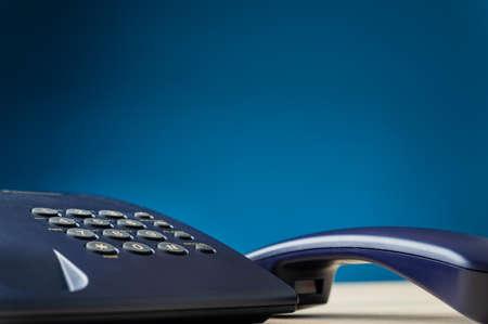 Closeup of black landline telephone with handset off the hook. Over navy blue background.