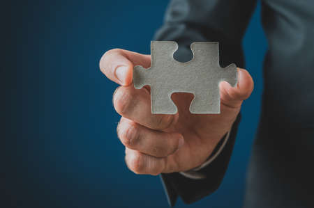 Closeup of businessman showing a blank puzzle piece with blue copy space on the left side of the image. Фото со стока