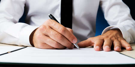 Wide view closeup image of businessman signing a document or contract. Фото со стока