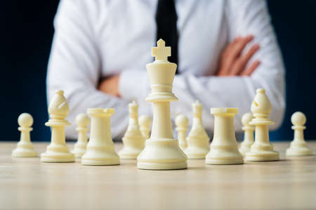 Business executive sitting confident at his desk with arms crossed and chess pieces positioned in front of him.