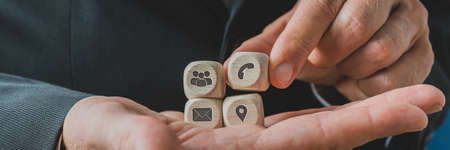 Wide view image of customer service representative holding wooden dices with contact information icons on them in the palm of his hand.