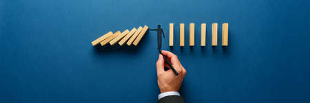 Wide view image of male hand drawing silhouette of a man making a stop gesture to prevent wooden dominos from collapsing. Over navy blue background.