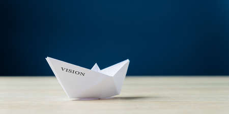 Paper made origami boat with the word Vision on it. Over navy blue background.