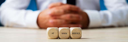 Customer service representative sitting behind wooden dices carrying an At your service sign. Wide view image.