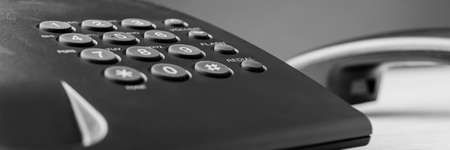 Wide view image of black landline telephone keypad with handset in background off the hook.