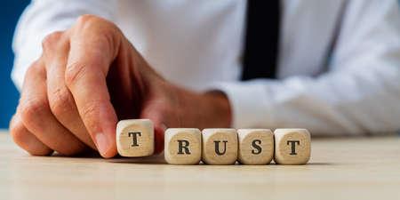 Hand van een zakenman die het woord Trust assembleert, gespeld op houten dobbelstenen.