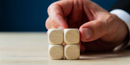Hand of a businessman stacking four blank wooden dices on a desk in a conceptual image.