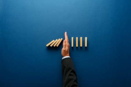 Bovenaanzicht van zakenman hand stoppen vallende dominostenen in een conceptuele afbeelding van bedrijfscrisisbeheer. Stockfoto