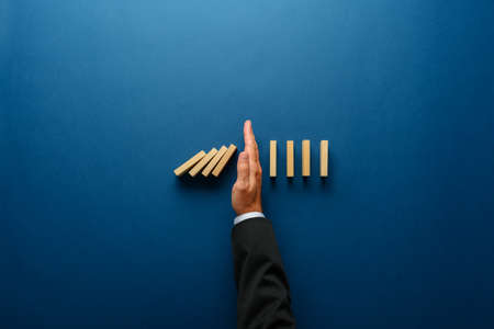 Vue de dessus de la main de l'homme d'affaires arrêtant la chute des dominos dans une image conceptuelle de gestion de crise commerciale. Banque d'images