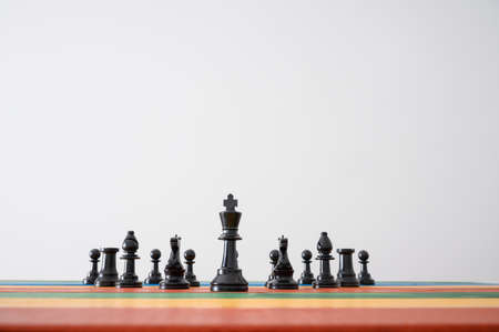 Black chess pieces positioned on colorful wooden desk with king figure as the leader in front of the others. Over grey background.