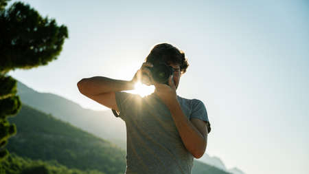 Low angle view of male photographer taking photo directly at you standing outside with rising sun glowing behind