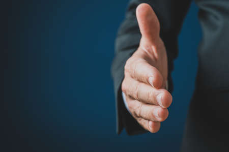 Hand of a businessman reaching to offer a handshake. Over navy blue background.