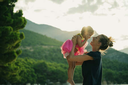 Happy young mother lifting her toddler daughter in pink skirt in the air in the morning as the sun rises from the hills in background.