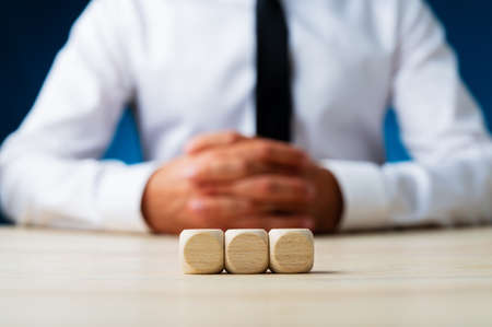 Three blank wooden dices in a row with blurred businessman in background.