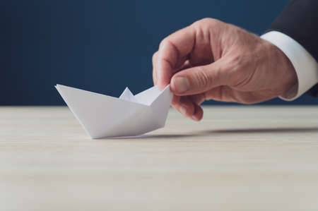 Hand of a businessman holding white origami paper made boat in a conceptual image of business vision.