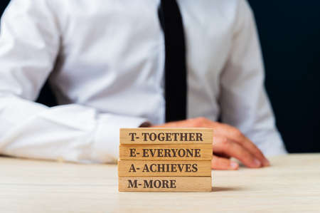 Team - together everyone achieves more sign on stacked wooden pegs wit businessman sitting in background.