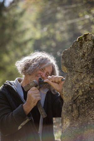 Happy senior sculptor working outside carving in stone using mallet and a chisel. 스톡 콘텐츠