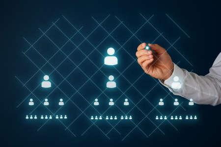 Netwerkmarketingconcept met zakenman die mensenpictogrammen en piramidespel trekt op virtuele interface met een gloeiende styluspen. Stockfoto