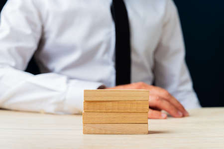 Businessman sitting at his desk with four stacked wooden pegs on it.