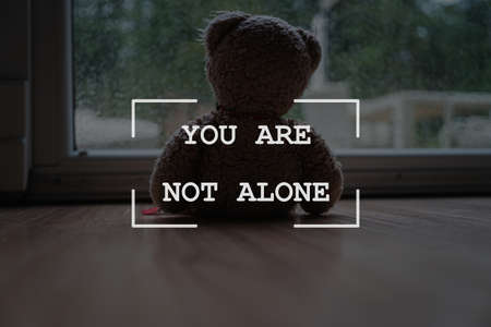 You are not alone sign over a teddy bear toy sitting by a large window looking out in a conceptual image.