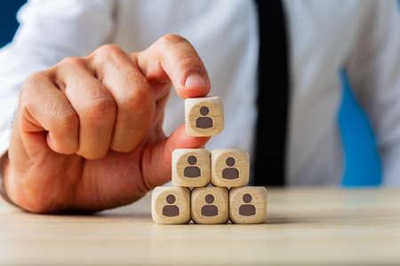 Business Executive Stapeln von Holzwürfeln mit Menschensymbolen auf ihnen in Pyramidenform in einem konzeptionellen Bild.