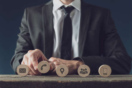 Front view of business customer service representative placing five wooden circles with contact and information icons in a row. Stock Photo