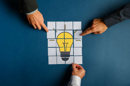 Top view of hands of three businessmen assembling a lightbulb drawn on post it papers. Over navy blue background.