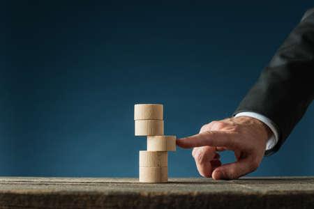 Hand eines Geschäftsmannes, der in einem konzeptionellen Bild der Geschäftsstabilität einen mittleren runden Stift in einen Stapel drückt.