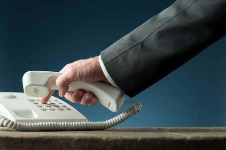 Hand of a businessman holding telephone handset dialing phone number on white landline telephone. Over navy blue background.