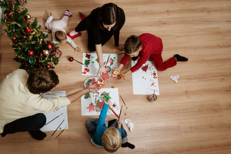 Top view of family of five sitting on living room floor next to a christmas tree making holiday ornaments and decoration together.