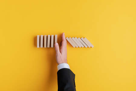 Top view of business crisis manager stopping falling dominos with his hand in a conceptual image. Over yellow background with copy space.