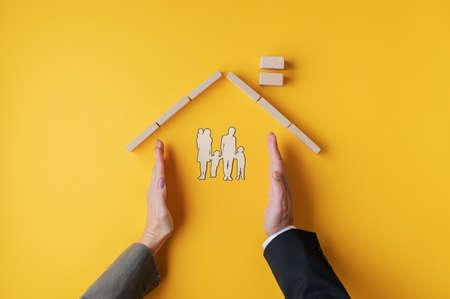 Männliche und weibliche Hände, die platziert werden, um ein Zuhause für die Scherenschnitt-Silhouette einer Familie in einem konzeptionellen Bild zu bilden. Über gelbem Hintergrund. Standard-Bild
