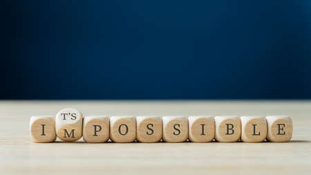 Word impossible spelled on wooden dices with the second one turning to spell the Its possible sign. Foto de archivo