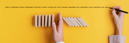 Female hand writing word of business development and success above a businessman stopping falling dominos in a conceptual image. Over bright yellow background. Archivio Fotografico