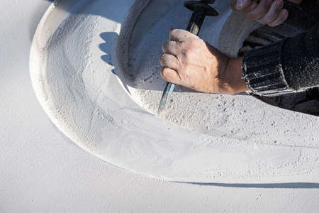 Closeup of an artist carving curves into a white stone with precise gestures using a chisel.
