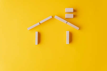 House made of wooden pegs on yellow background in a conceptual image of insurance or ownership. With copy space. Imagens