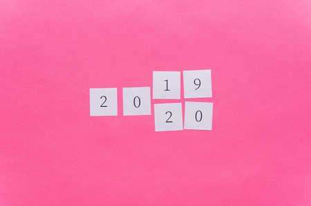 2019 written on white note papers changing the last two digits to 2020 in a conceptual image of the coming new year. Over pink background with copy space. 版權商用圖片