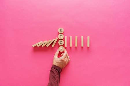 Männliche Hand, die fallende Dominosteine unterbricht, indem sie das Stoppwort auf hölzernen Schnittkreisen dazwischen platziert. Über rosa Hintergrund mit Kopienraum. Standard-Bild