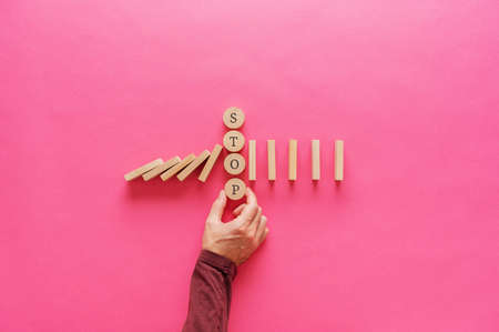 Male hand interrupting falling dominos by placing stop word spelled on wooden cut circles in between. Over pink background with copy space.
