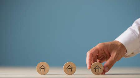 Mano masculina colocando tres círculos de madera cortada con forma de casa sobre ellos en una fila en una imagen conceptual del mercado inmobiliario. Sobre fondo azul con espacio de copia. Foto de archivo