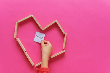 Heart shape made of wooden pegs with child hand placing note paper with Family written on it inside the heart. Over pink background.